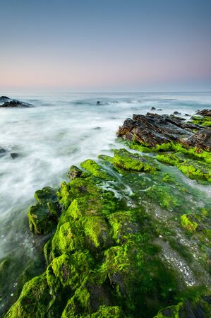 Impressive sunrise in a beach of Malaga, Andalusia with long exposure water and green rocks in firts place