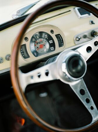 view through the window of a yellow classic car with wooden steering wheel