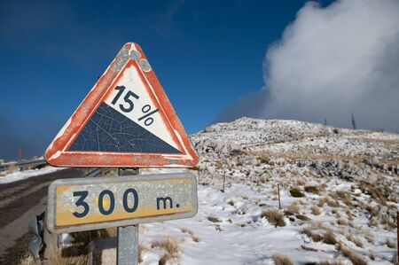 triangular sign indicating the unevenness of a high mountain road. Background with snow in the background