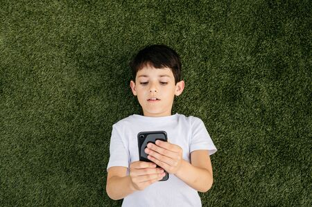smiling boy lying on the grass at home playing with the mobile Imagens