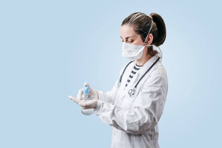 view of a doctors hands disinfecting his hands with hydroalcoholic gel gloves and mask with everything needed to fight the coronavirus pandemic