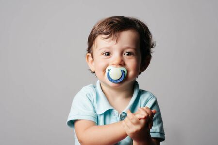 smiling two-year-old looking at camera with pacifier in mouth in grey background