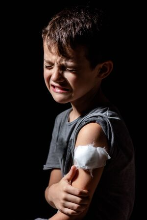 Cute little boy with sticking plaster on arm on black background