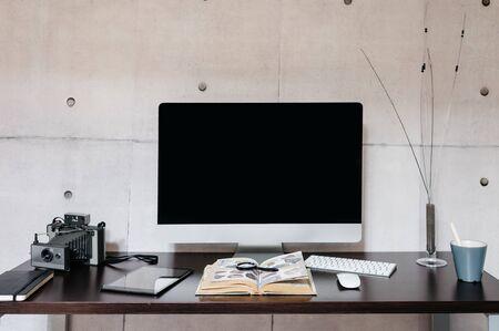 A desk with a computer on a table Foto de archivo