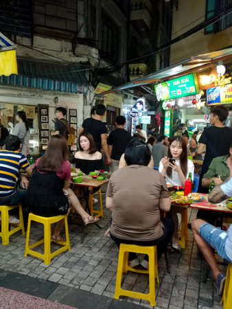 People dining in a busy restaurant street in Hanoi city.