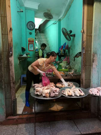 Butcher sorts trays of poultry for sale