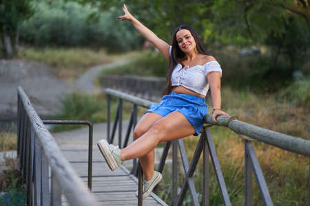 Pretty and happy woman in blue pants and white top sitting on a walkway next to a river in summer 版權商用圖片