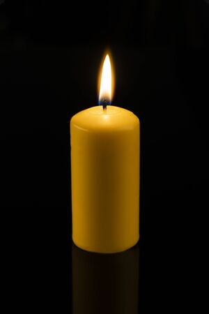 Long, round, yellow wax candles lit on a dark, black background.