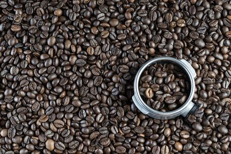 Background of roasted coffee beans and a professional coffee maker filter holder full of coffee. Stok Fotoğraf