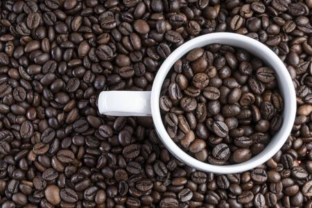 Background of roasted bean coffee with a white cup full of bean coffee on one side