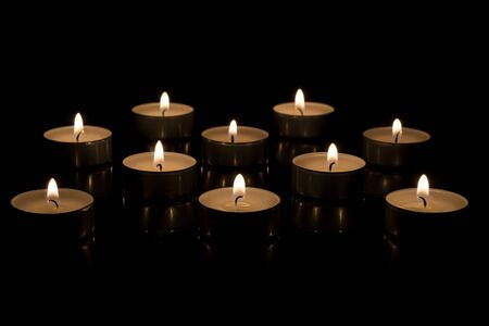 Small round candles lit in a dark candle holder on a black background Stok Fotoğraf