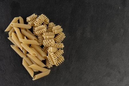 Two piles of Italian pasta, macaroni and spirals together on a slate plate.