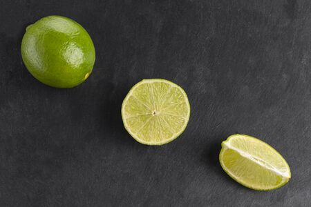 fresh whole and cut lime isolated on a slate plate