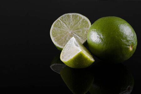 fresh whole and cut lime isolated on black background.