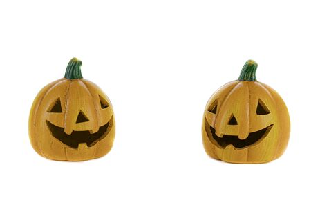 Two orange ceramic pumpkins with eyes, nose and isolated mouth on a white background. Halloween concept.