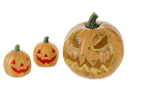 Two orange ceramic pumpkins with red eyes and mouth and a large pumpkin with eyes and mouth, isolated on a white background. Halloween concept. 版權商用圖片