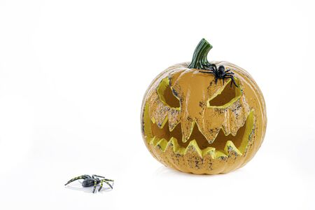 Big orange pumpkin with eyes and mouth and two spiders, isolated on a white background. Halloween concept. 版權商用圖片
