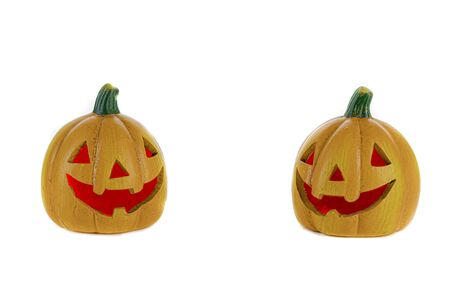Two orange ceramic pumpkins with nose eyes and mouth red isolated on a white background. Halloween concept.