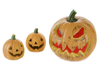 Two orange ceramic pumpkins with eyes nose and mouth and a large pumpkin with eyes and mouth with red light, isolated on a white background. Halloween concept. 版權商用圖片