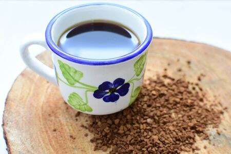 Cup of coffee, accompanied by coffee beans on wooden background