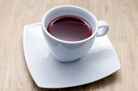 Hot red berry tea in white cup