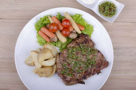 beef with salad, rustic potatoes and chimichurri