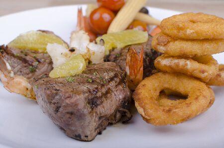 beef with salad, shrimp, onion rings and chimichurri 版權商用圖片