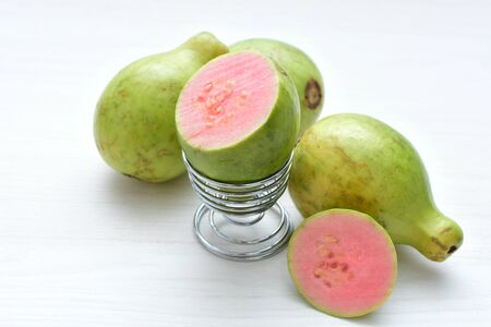 Whole and sliced natural ripe guava fruit with reddish texture