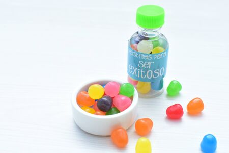 Didactic representation of jars and candies of positive phrases for life of multicolors and green cover