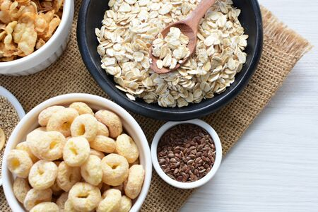 Granola with cereal, raisins, coconut accompanied by quinoa and flaxseed seeds on light background 写真素材