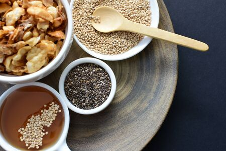 Granola with cereal, raisins, coconut accompanied by quinoa and linseed seeds on dark background 写真素材