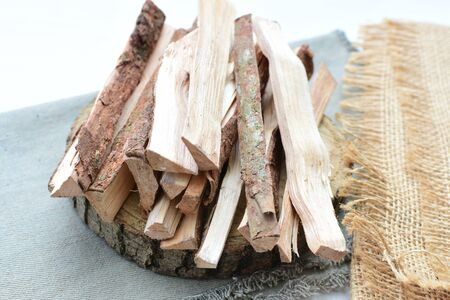 wooden sticks - firewood, placed on a tidy and cluttered flat surface on white wooden background