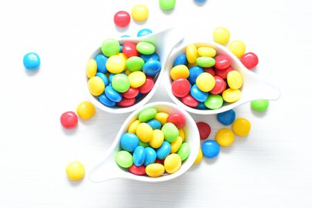 Variety of blue, red, green, yellow multicolored candies displayed in containers