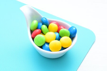Variety of blue, red, green, yellow multicolored candies displayed in containers Фото со стока
