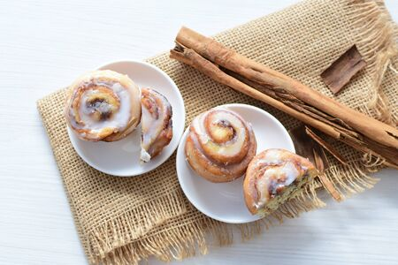 Delicious homemade small cinnamon rolls with melted sugar on light background