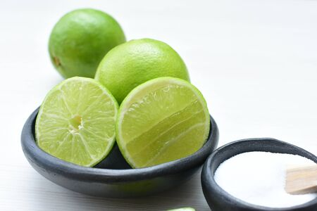 (Citrus - latifolia, the Persian lemon, whole and in pieces tahiti lemons accompanied by salt with an intense green