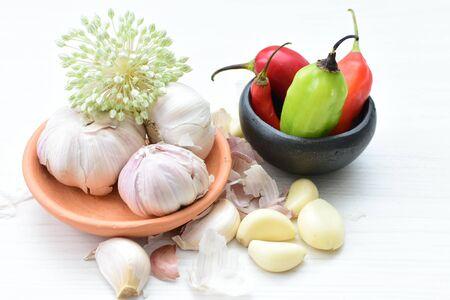 Allium sativum - Whole and minced garlic accompanied by garlic flower on decorated flat background