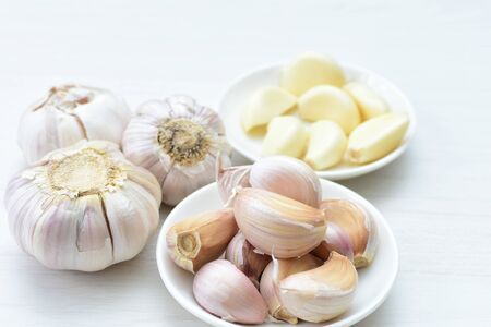 Allium sativum - Whole garlic, minced and shelled displayed in containers on light backgrounds