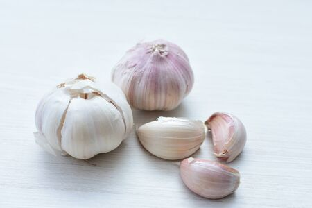 Allium sativum - diversity of whole, minced and watered garlic with peel on flat bottom