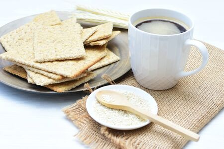 Soda biscuits with healthy sesame whole and in pieces accompanied by a cup of coffee with honey and jam
