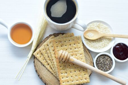 Soda biscuits with healthy sesame whole and in pieces accompanied by a cup of coffee with honey and jam 版權商用圖片