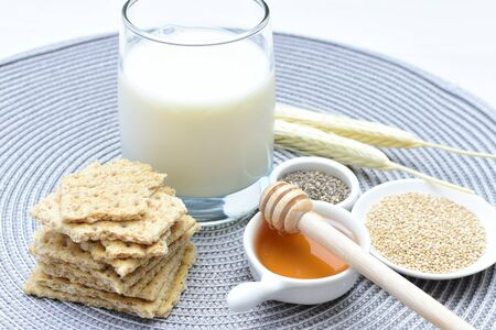 Soda biscuits with healthy sesame whole and in pieces accompanied by a glass of milk and honey and seeds