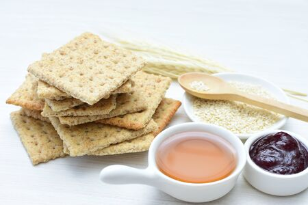 Soda biscuits with healthy sesame whole and in pieces accompanied by honey, jam and seeds on a flat background