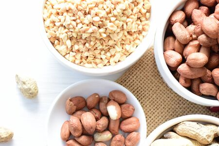 Arachis hypogaea - Peanut variety in seed, whole and crushed peanuts displayed in containers on white wooden background Stock Photo