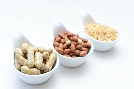 Arachis hypogaea - Peanut variety in seed, whole and crushed peanuts displayed in containers on white wooden background