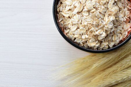 Avena sativa - Natural rolled oats, displayed in containers on wooden background