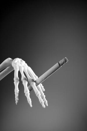 tabaco: cráneo mano y cigarret Foto de archivo