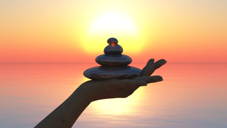 zen stones in hand and sunset at sea
