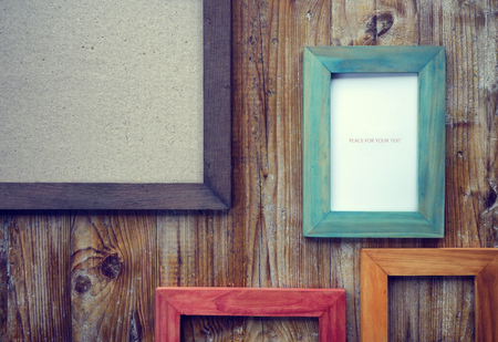 photo pictures: picture frames of different colors and wooden background Stock Photo