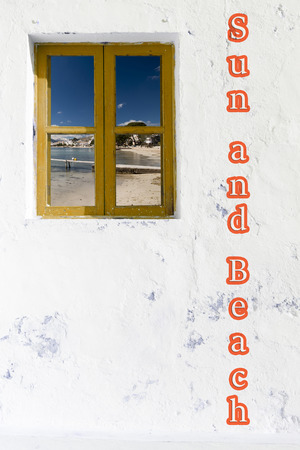 beach window: White wall facade with wooden window and sun and beach letters